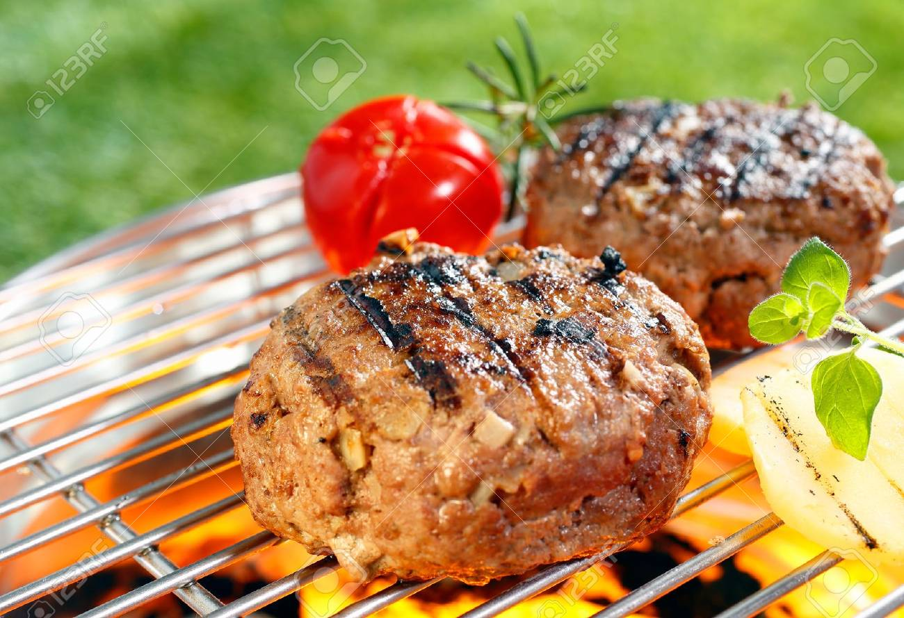 Beef burgers cooking on grilling pan outdoors - 18566125