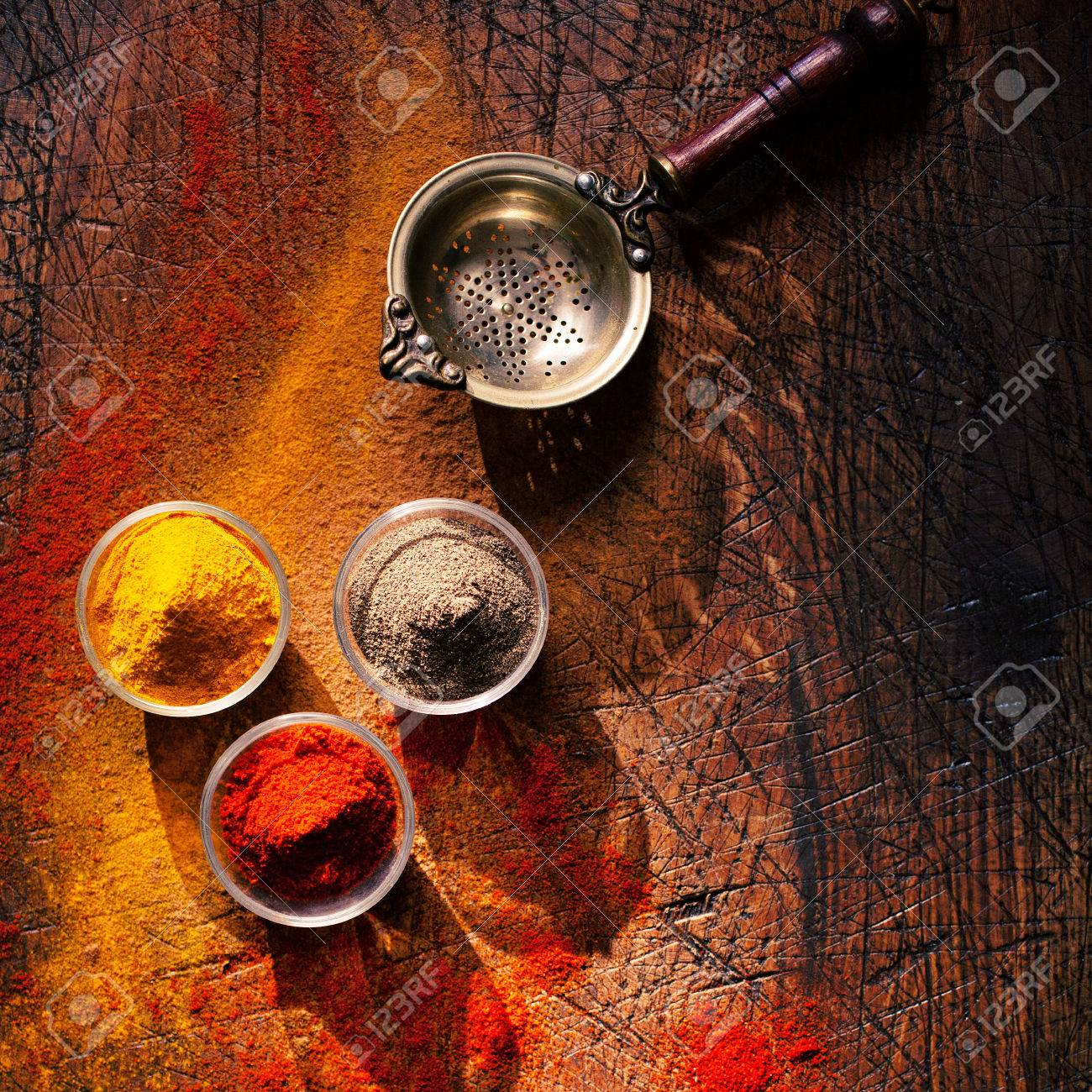 Overhead view of three bowls of spice in a country kitchen on an old scored wooden surface with scattered powder and an old retro strainer or sieve Stock Photo - 22230439