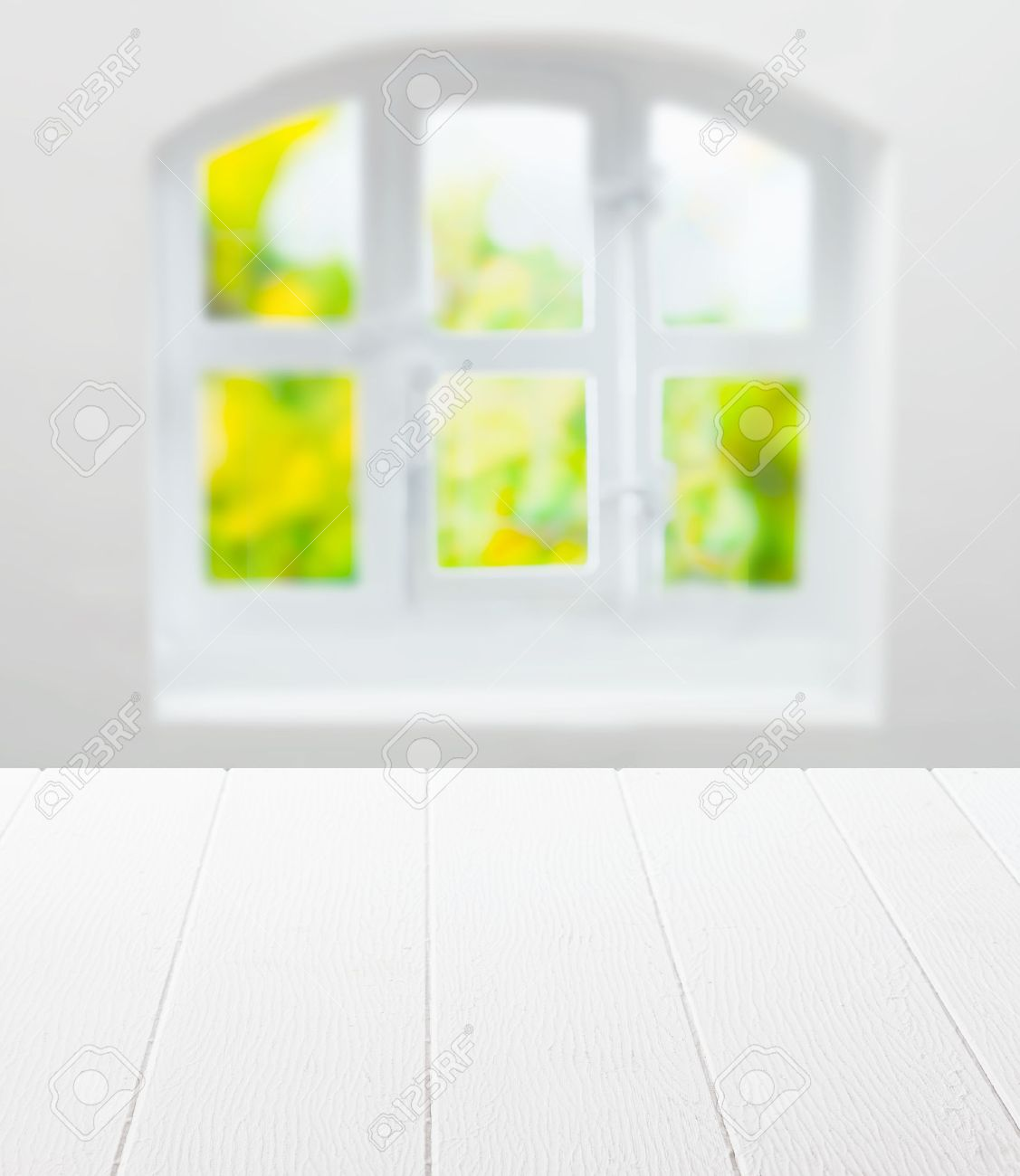 25032179 Empty clean white kitchen table in front of a cottage pane arched window with a view of greenery in  Stock Photo