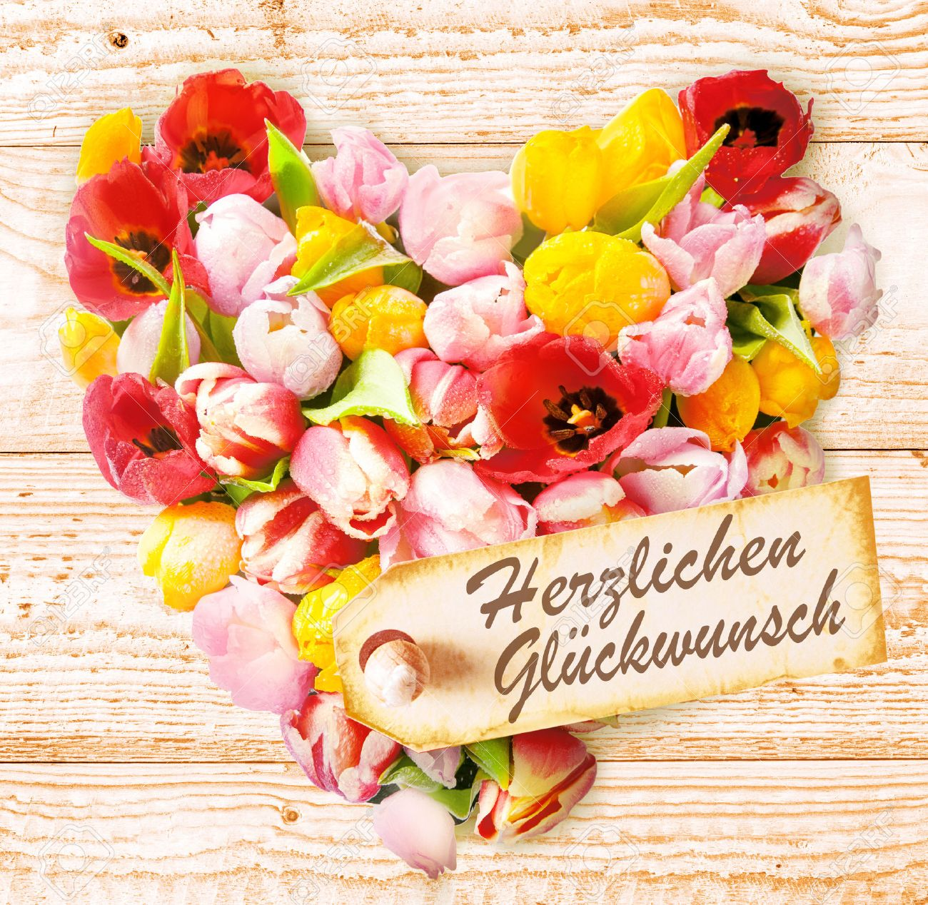German Birthday Wishes On A Colourful Floral Heart Formed Of Fresh Spring Tulips In Vibrant Colours
