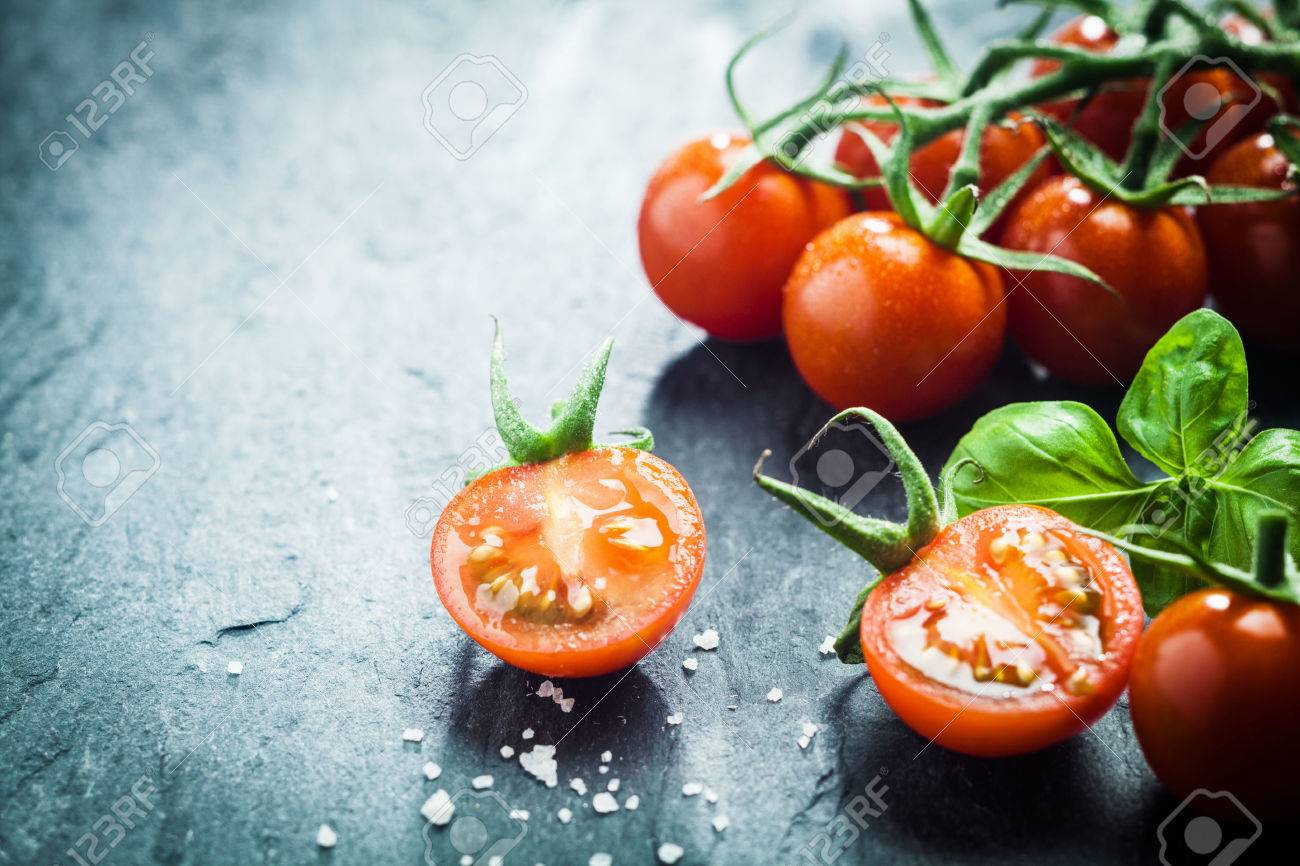 Fresh grape tomatoes with basil and coarse salt for use as cooking ingredients with a halved tomato in the foreground with copyspace - 27053500