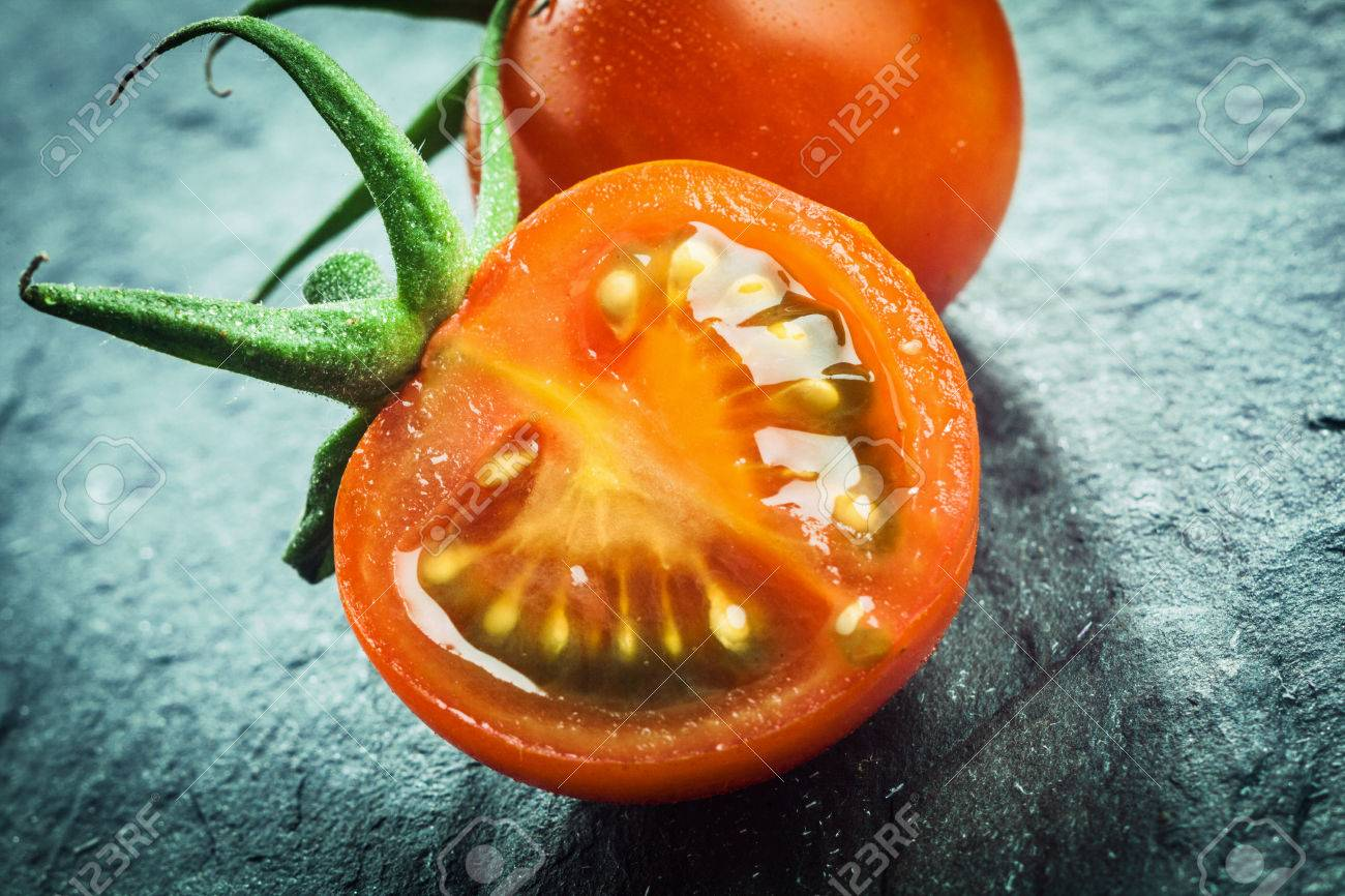 Close up of a halved juicy fresh grape tomato showing the pips and pulp with a green stalk for a healthy salad or cooking ingredient Stock Photo - 27053501