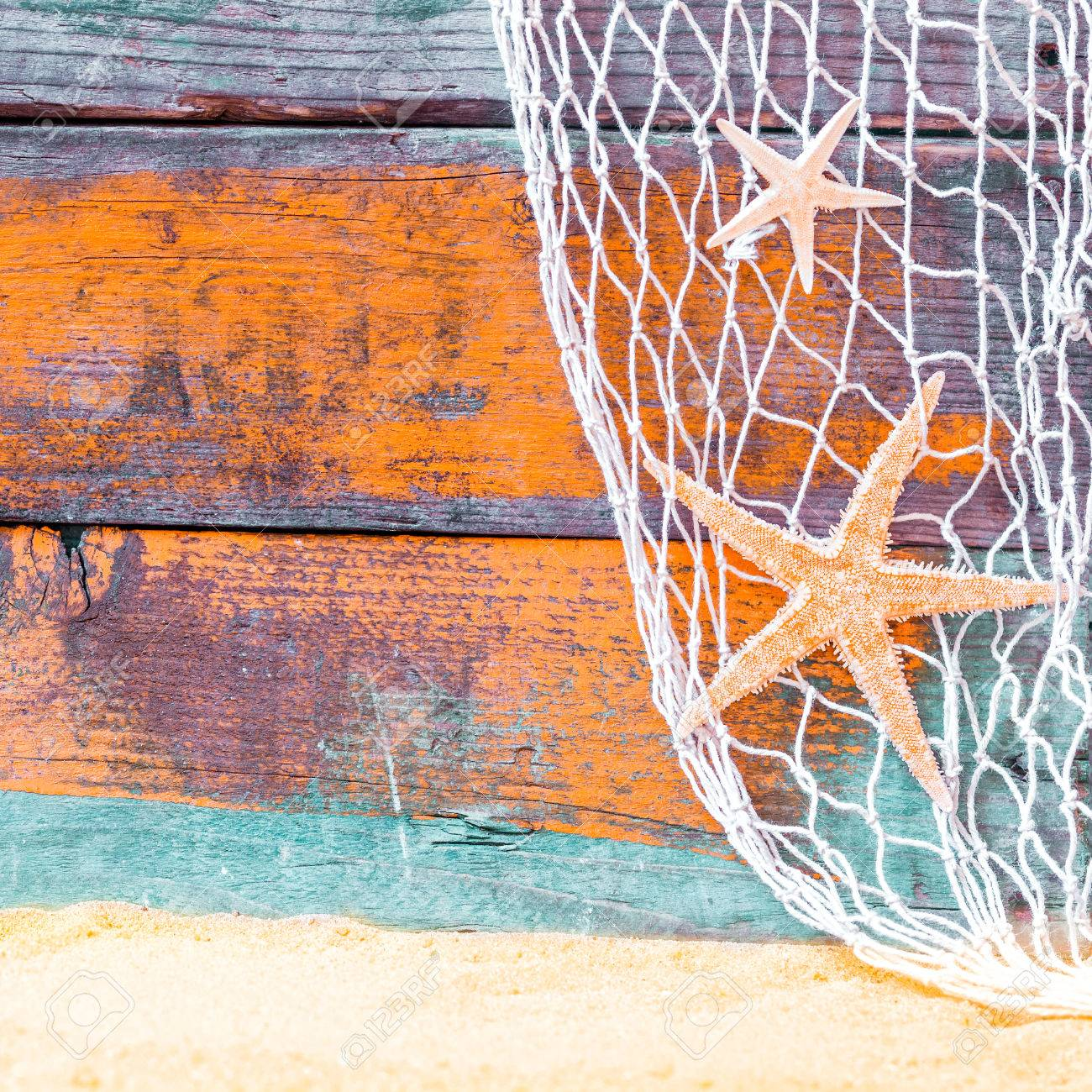 Rustic Nautical Background With Starfish Hanging In A Fishing Net Against Weathered Painted Wooden Boards
