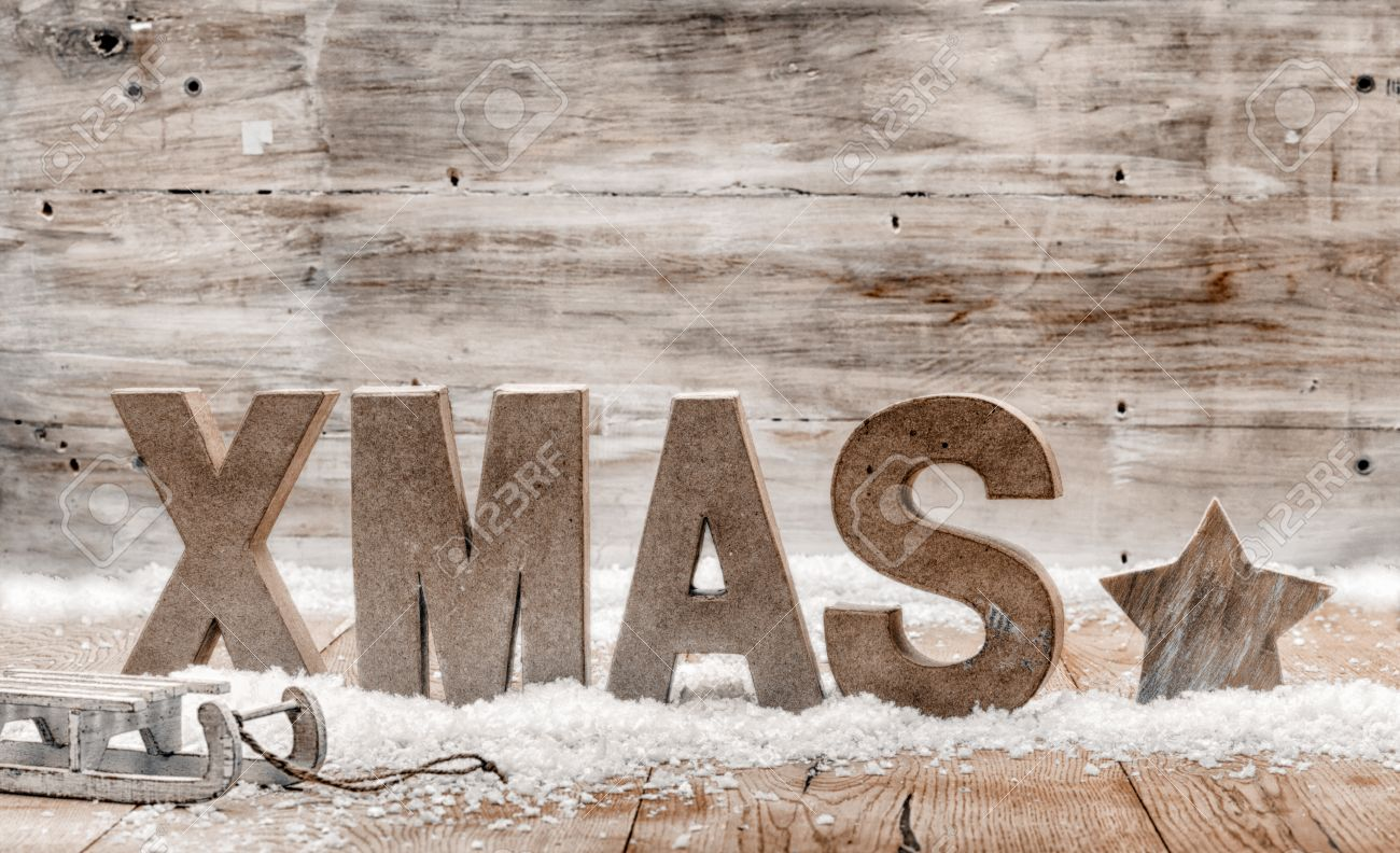wood craft rustic christmas background with wooden letters spelling xmas standing in snow with a star