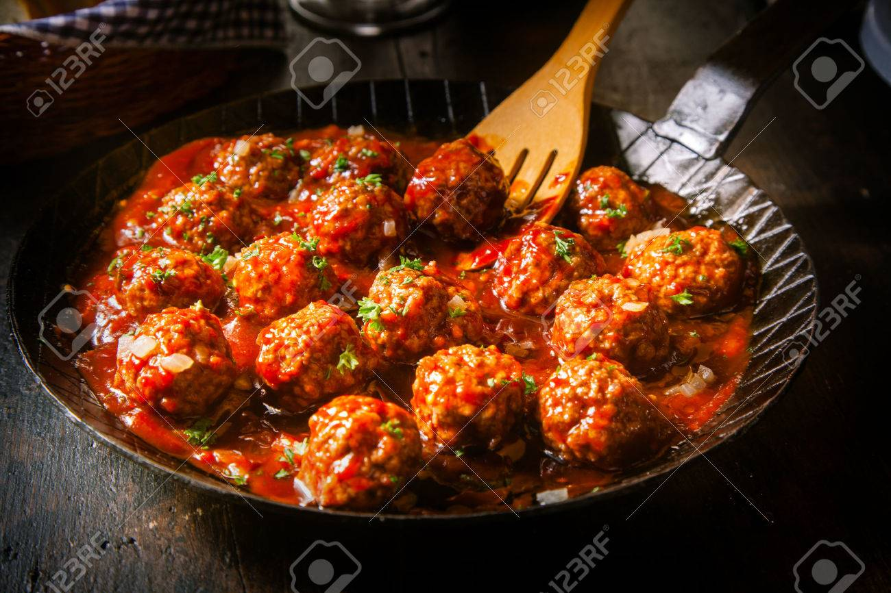 Delicious meatballs made from ground beef in a spicy tomato sauce served in a skillet or old metal pan in a restaurant - 35404683
