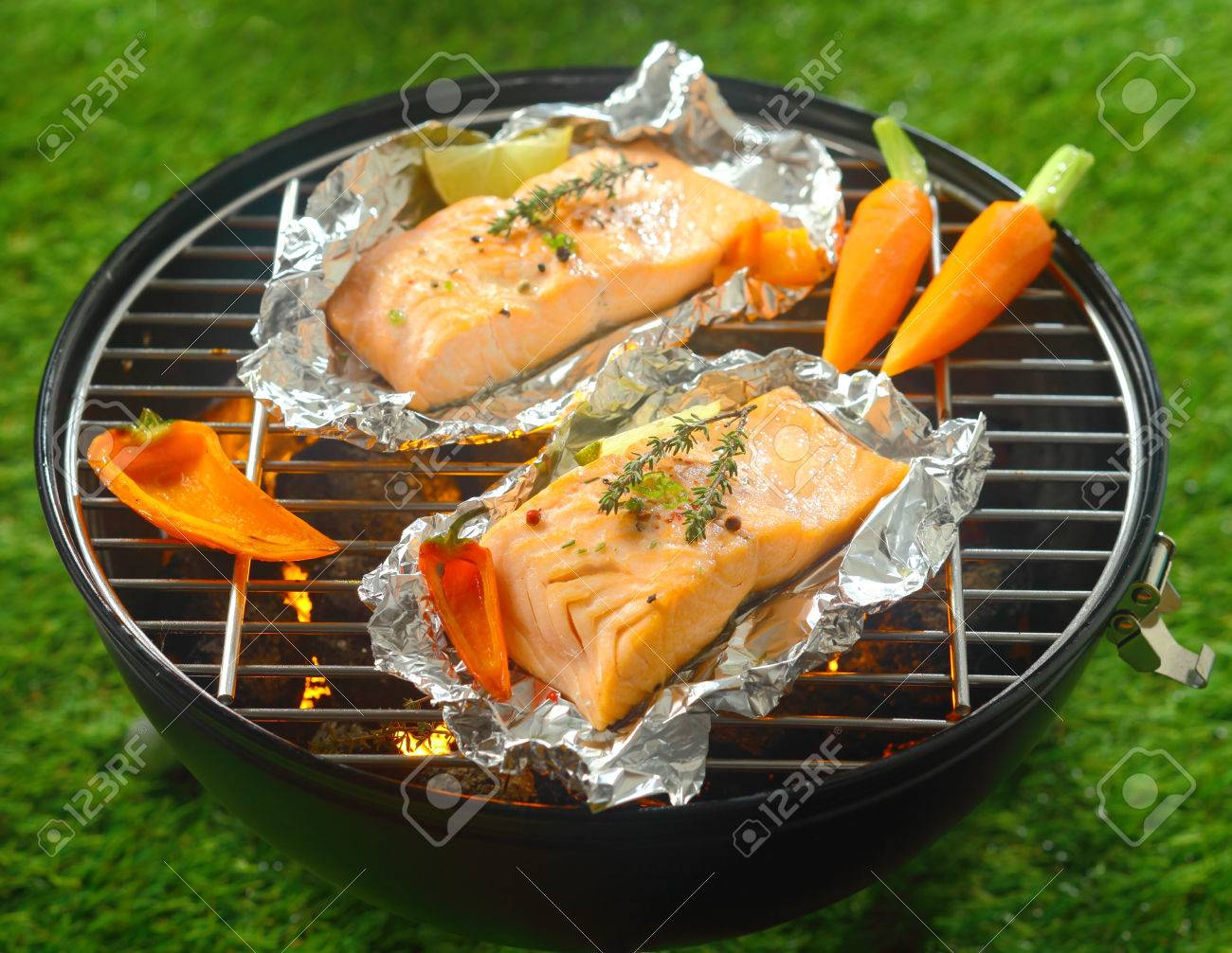 Grilled salmon steaks with baby vegetables cooking on tin foil grilled salmon steaks with baby vegetables cooking on tin foil over a barbecue outdoors in summer ccuart Gallery