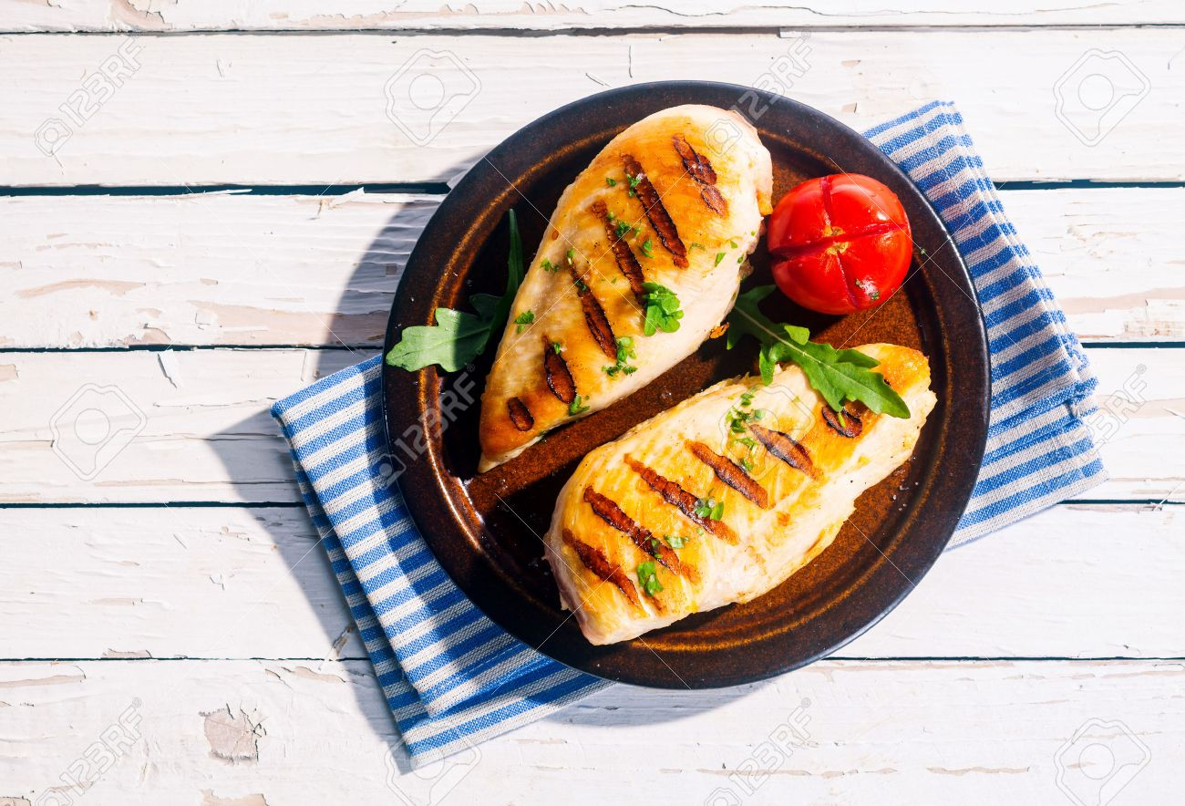 Two Delicious Fresh Grilled Chicken Breasts Seasoned With Herbs Served On A Plate With Tomato On