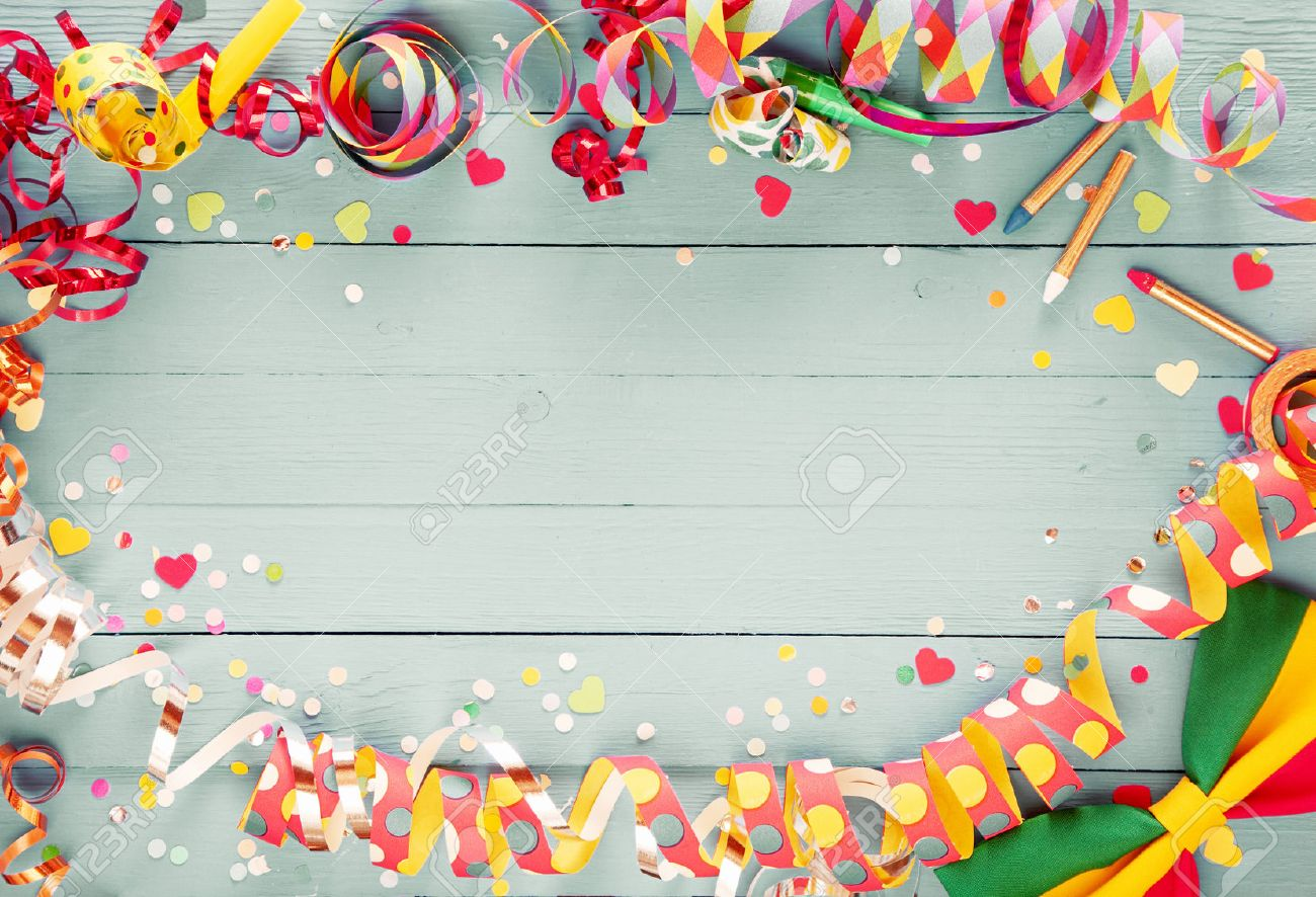 Colorful party frame with streamers and confetti and a vibrant bow tie in a corner around central copy space on a rustic wooden background - 51721201