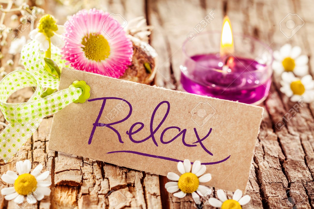 Cute relaxation display with handwritten relax sign set on tree bark surface decorated with various flowers and candle - 52284717