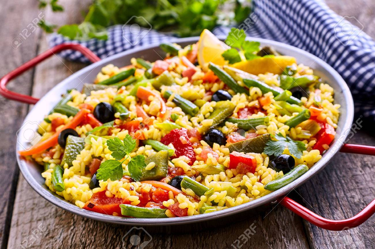 Close Up of Colorful and Fresh Vegetarian Paella Spanish Rice Dish Served in Pan with Red Handles and Linen Napkin on Rustic Wooden Table - 53500373