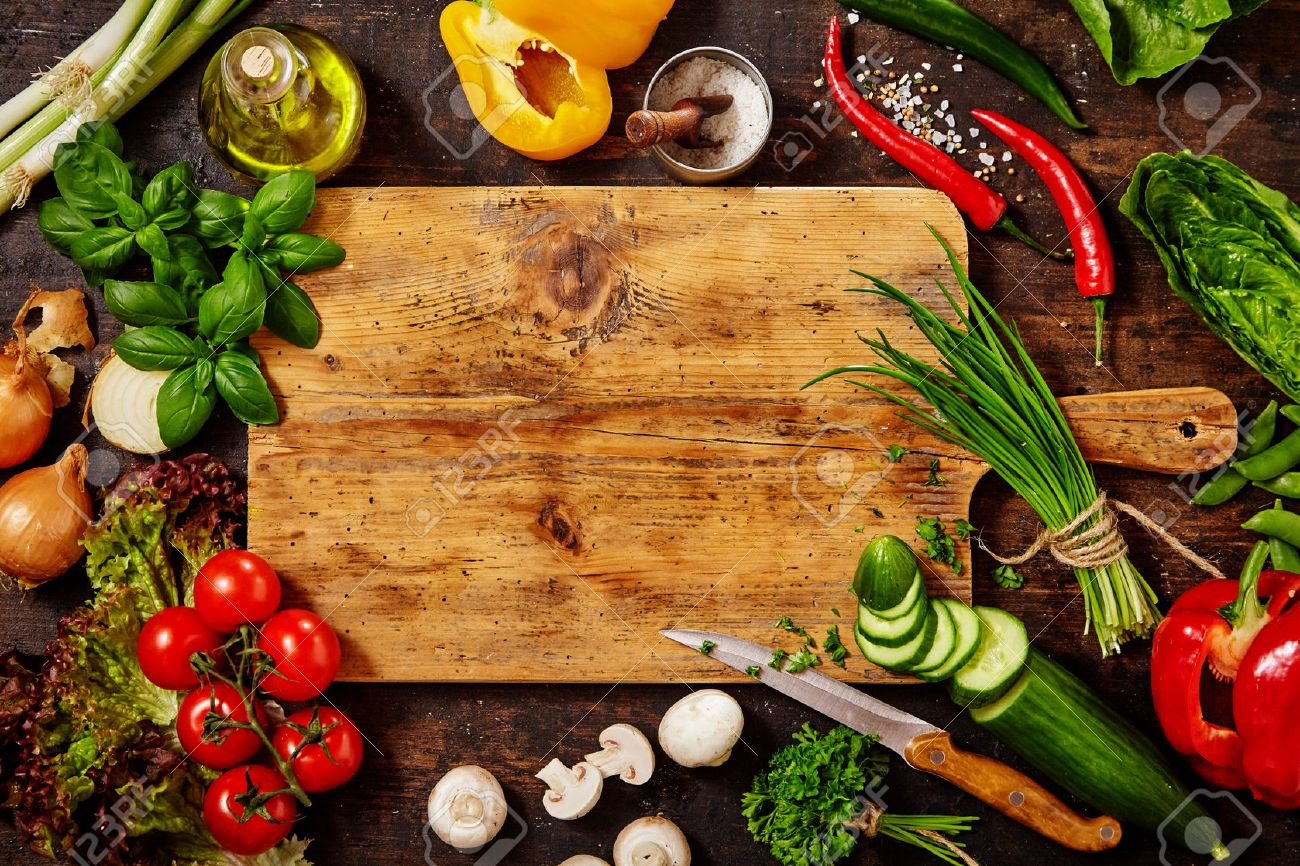 High Angle Still Life View of Knife and Wooden Cutting Board Surrounded by Fresh Herbs and Assortment of Raw Vegetables on Rustic Wood Table - 56707602