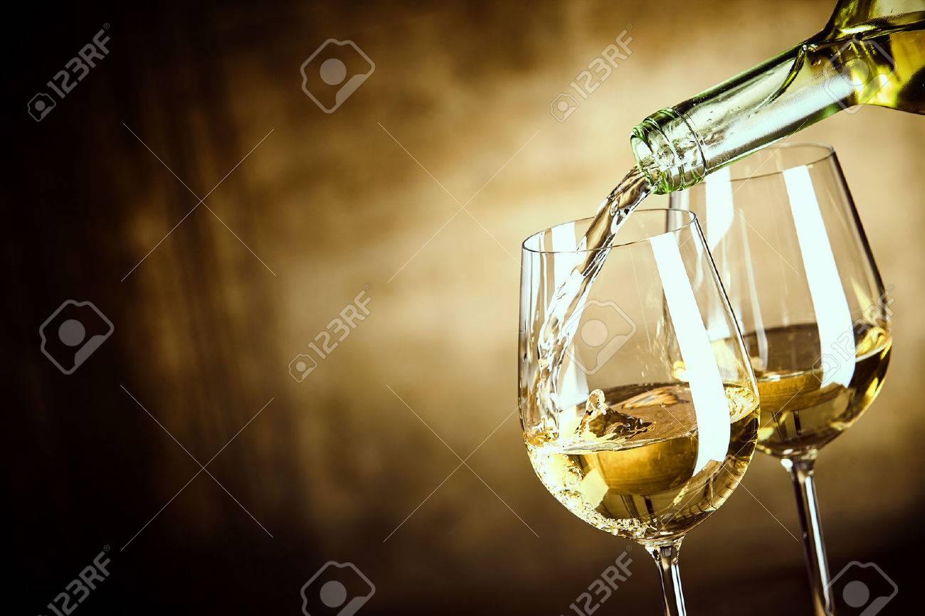 Pouring two glasses of white wine from a bottle in a close up view of the wineglasses over an abstract brown blue background with copy space - 57259324