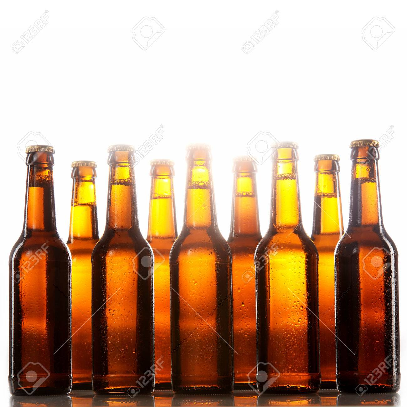 Tall beer bottles with no labels and metal caps stand two rows