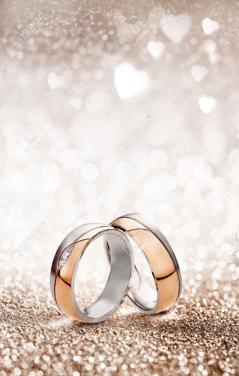 Romantic wedding ring celebration background with two gold rings balancing upright over a light sparkling background with white hearts and copy space for an invitation or greeting card - 62635664