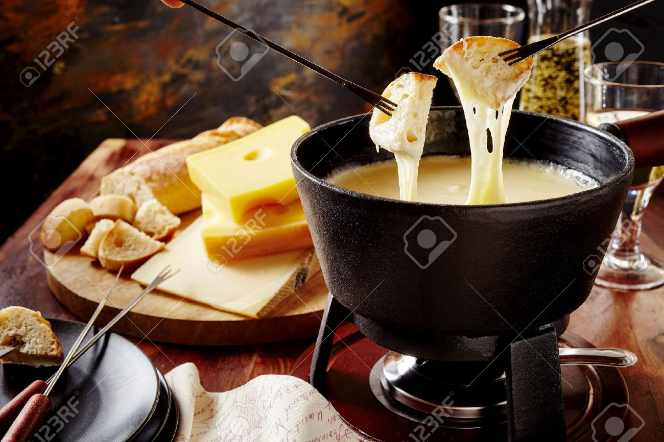 Gourmet Swiss fondue dinner on a winter evening with assorted cheeses on a board alongside a heated pot of cheese fondue with two forks dipping bread and white wine behind in a tavern or restaurant - 62635343
