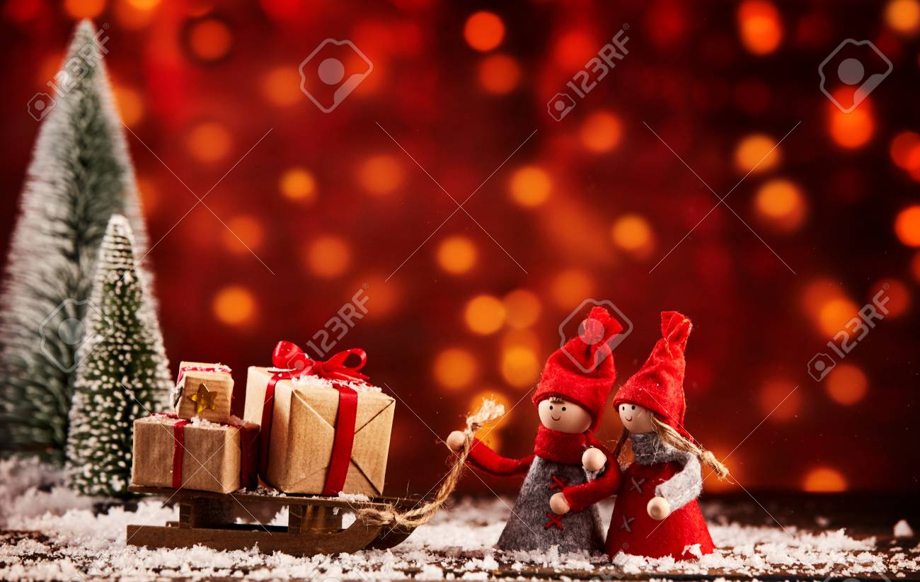 Two cute little Christmas figures with a sled full of gifts in a snowy winter landscape with colorful bokeh of warm toned lights and copy space - 113761018