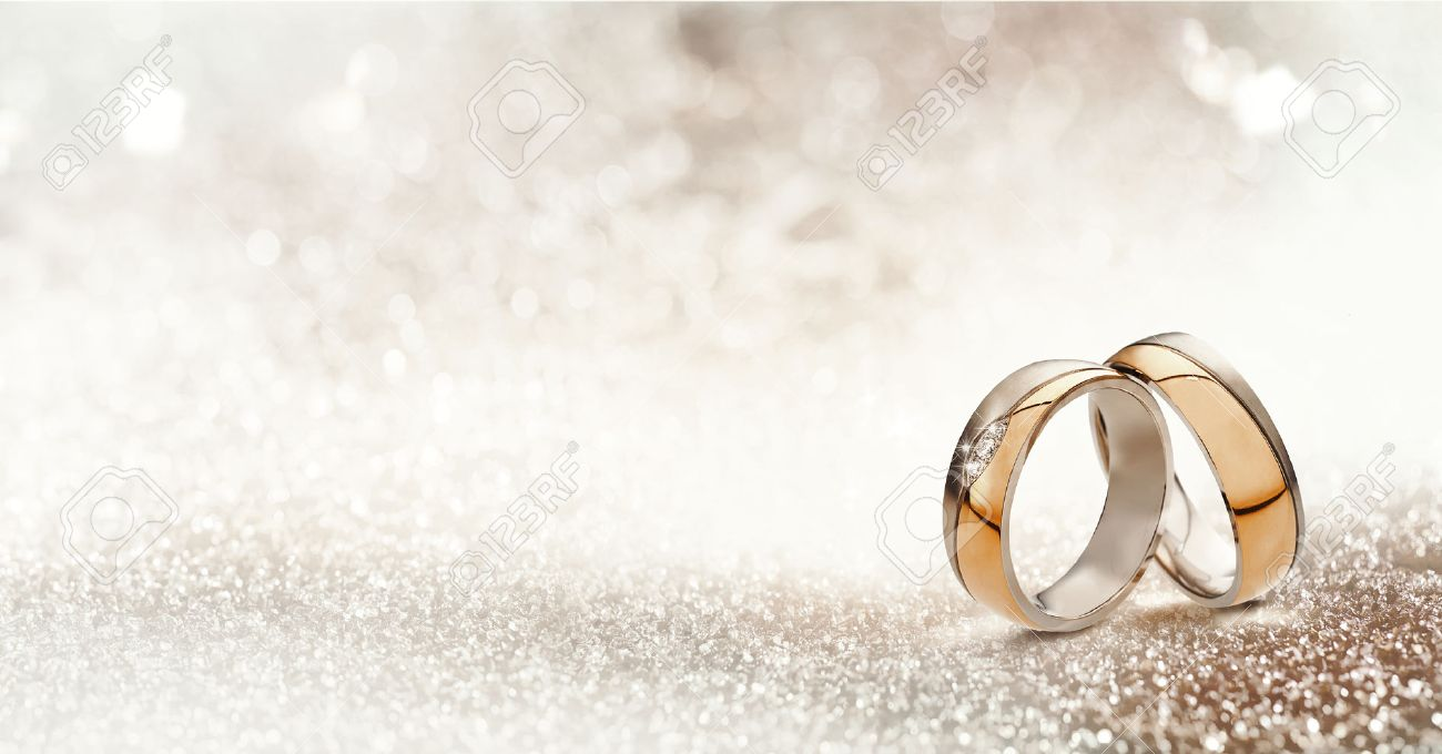 Panoramic banner of two upright gold wedding bands symbolic of love and romance on a textured glitter background with copy space for your greeting or congratulations - 65859237