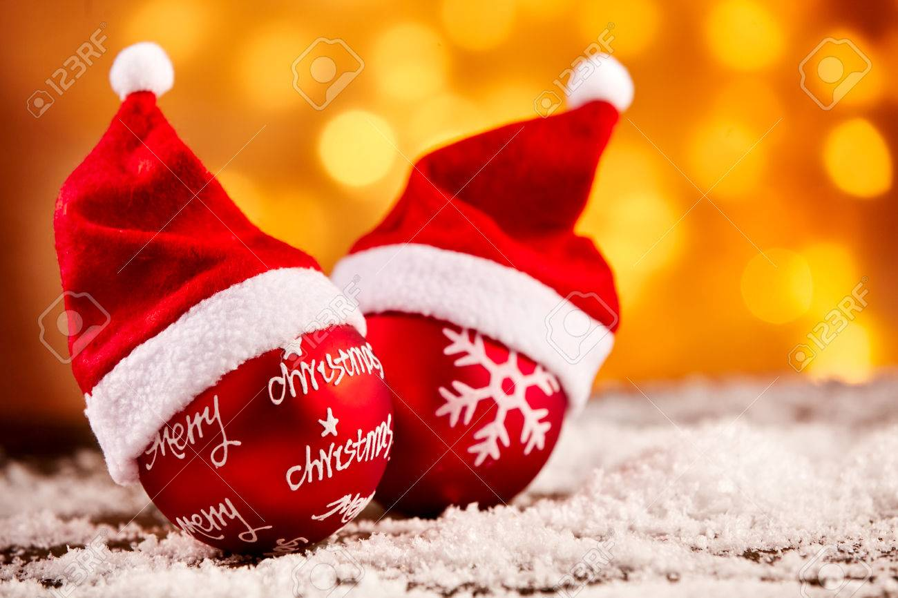 024d5cdd76ec3 Bright colorful Christmas decoration background with two decorative red  baubles dressed in Santa hats and a