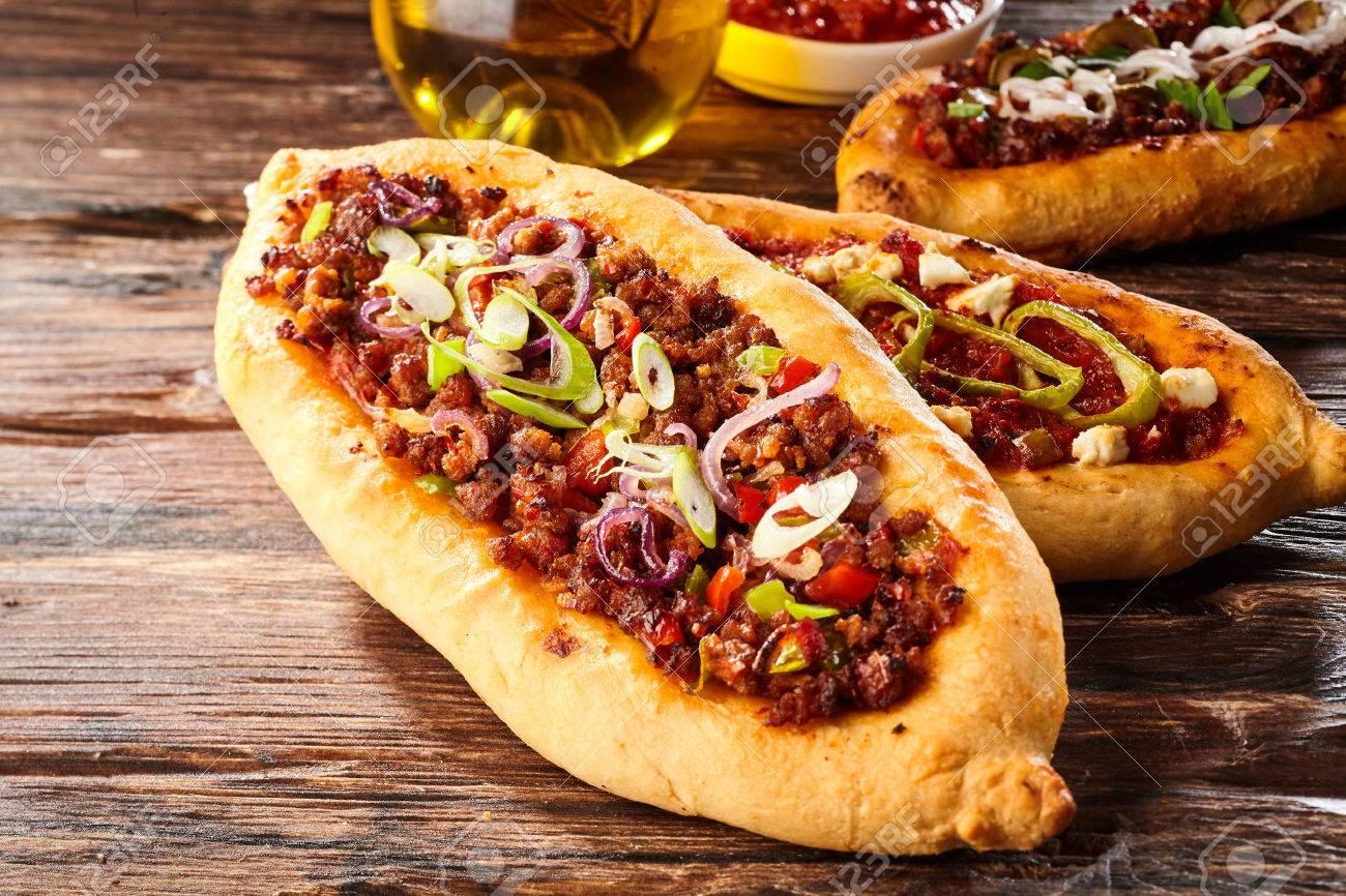 Drei Türkische Pide Pizza Laibe Mit öl über Abgenutzten Dunklen