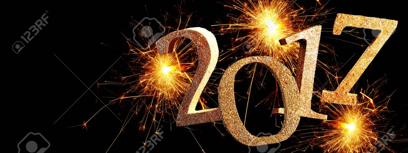 2017 new year banner with exploding fireworks and gold glitter date over a black midnight background