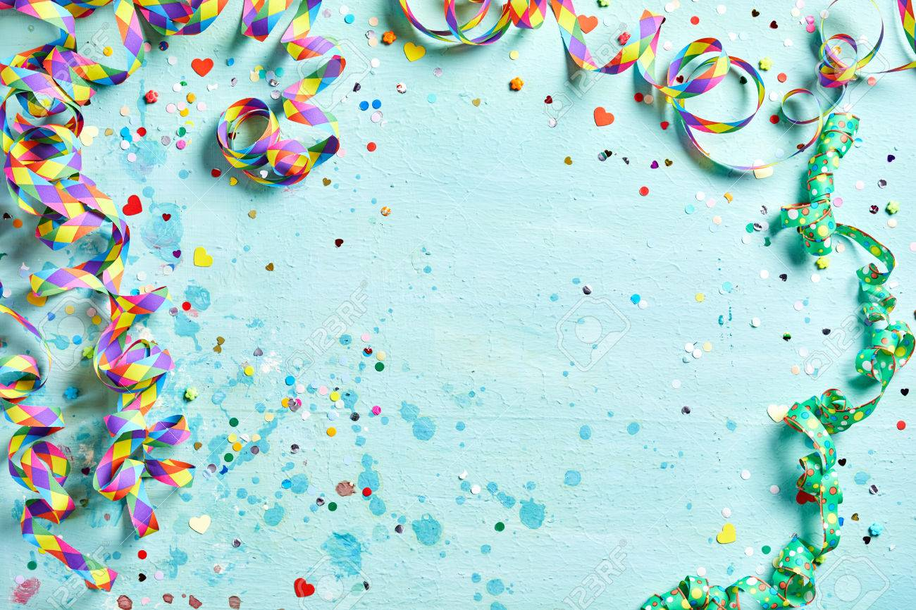 Festive party or carnival border of coiled streamers and confetti on a light blue green wood background with copy space - 69278499