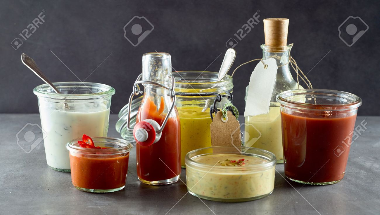Selection of assorted sauces and dressings in various containers to serve with takeaway or barbecued food including, relish, chili, ketchup,mayonnaise, mustard, and savory oil - 69399664