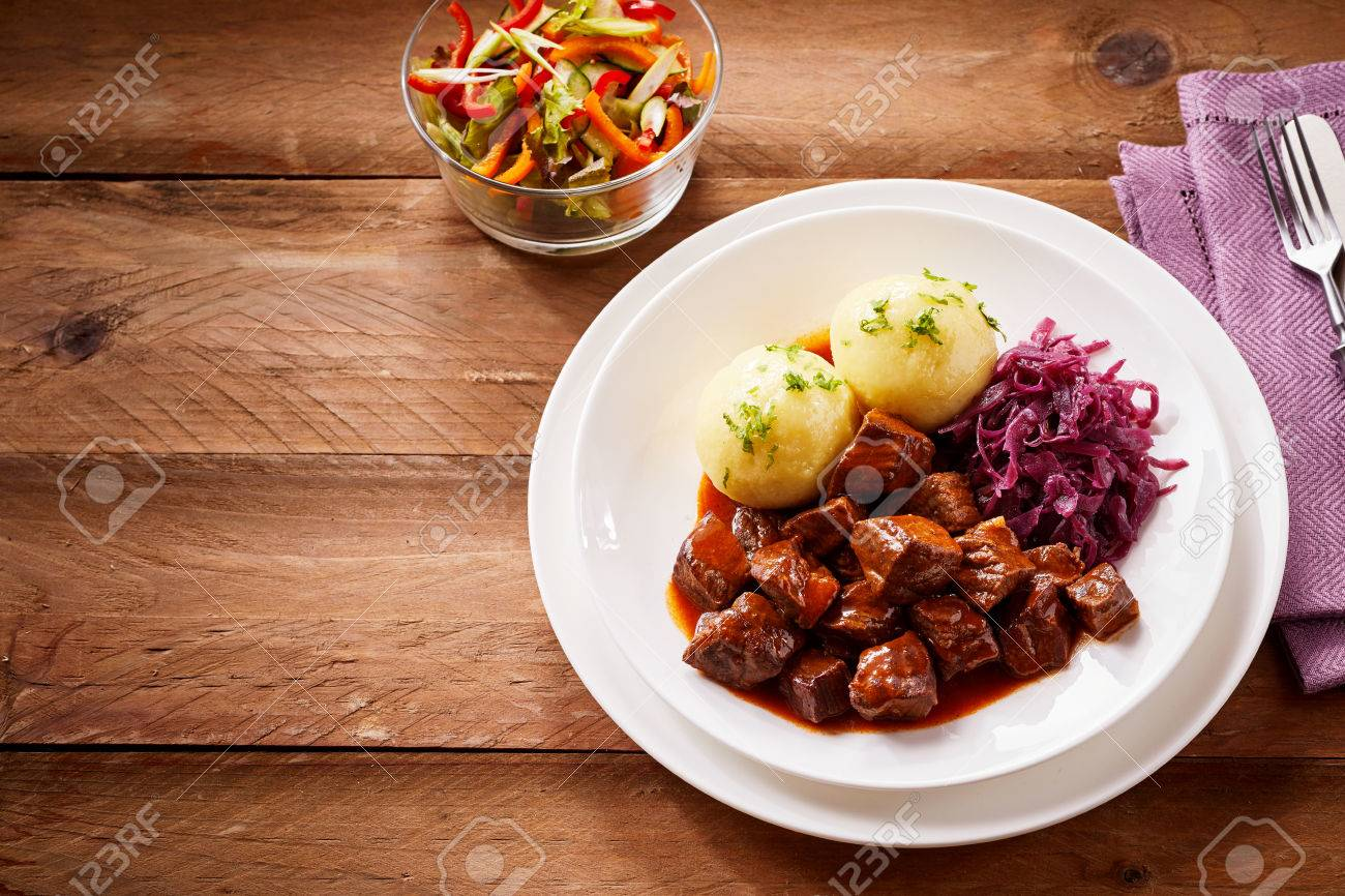 Traditional German Cuisine With Tasty Rich Beef Goulash And Boiled Dumplings Served With Shredded Purple Cabbage