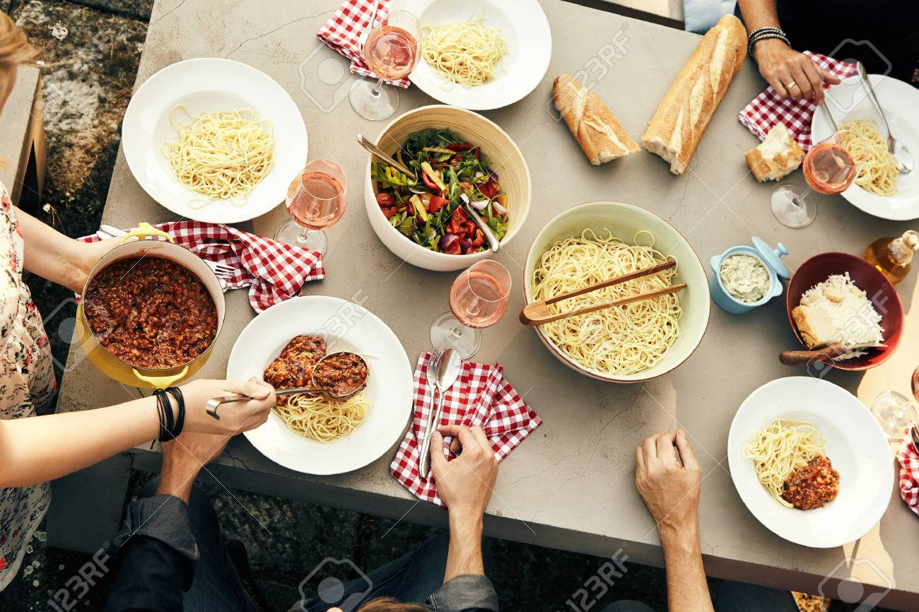 Group of friends enjoying a meal of spaghetti Bolognaise with tasty fresh salad and crusty bread at a picnic table outdoors, overhead view of their hands and the food Stock Photo - 74249126