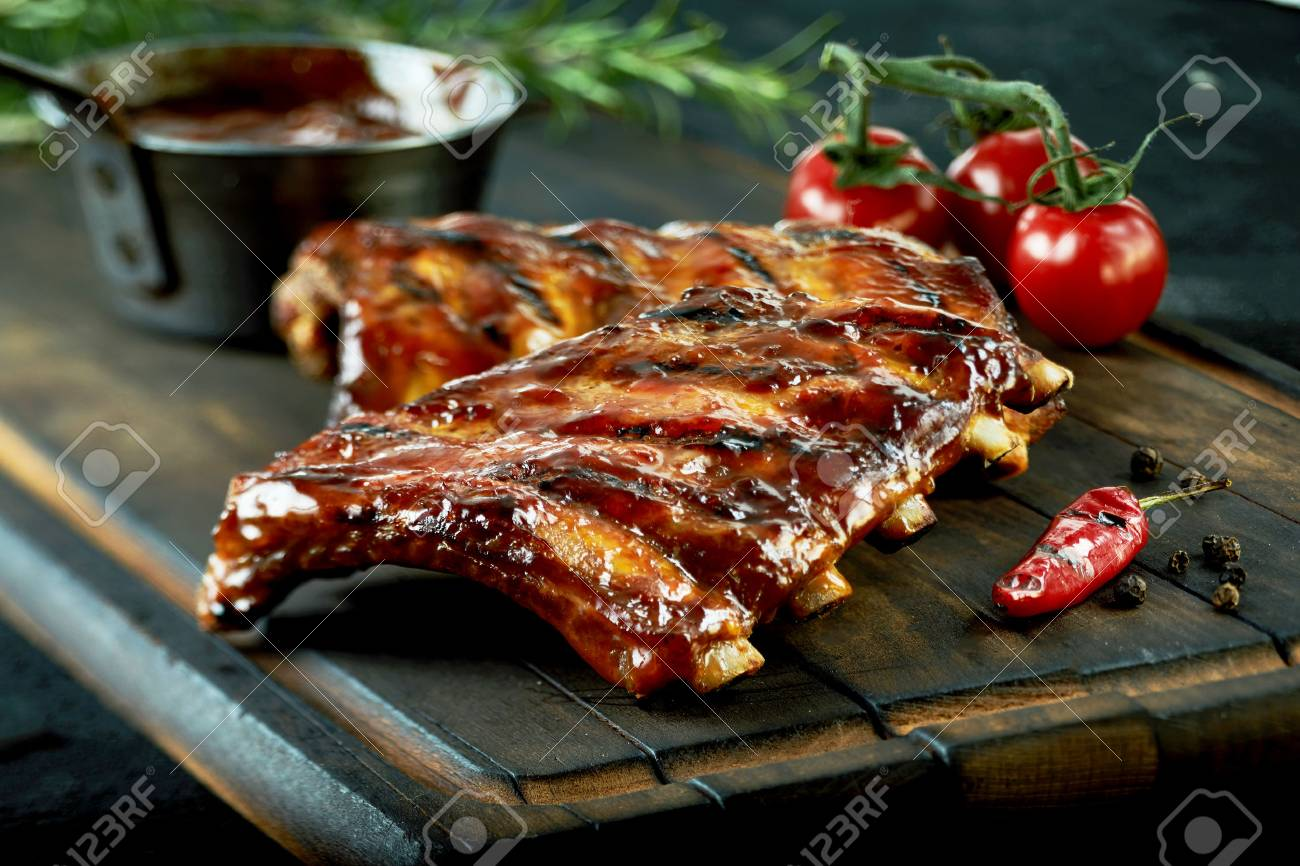 Spicy hot grilled spare ribs from a summer BBQ served with a hot chili pepper and fresh tomatoes on an old vintage wooden cutting board - 75988916