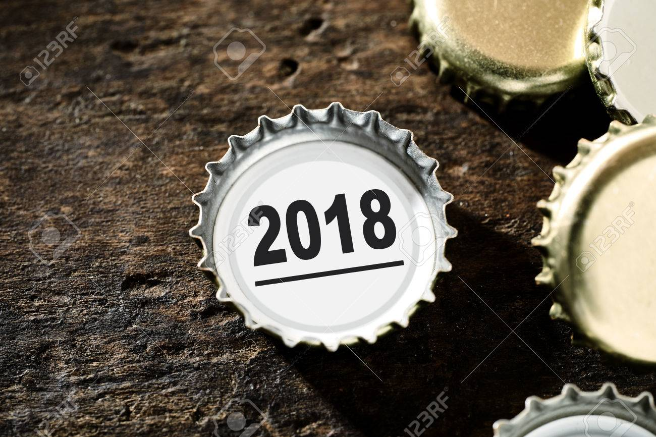 2018 new year background with a bottle top with the date lying on a rustic wood