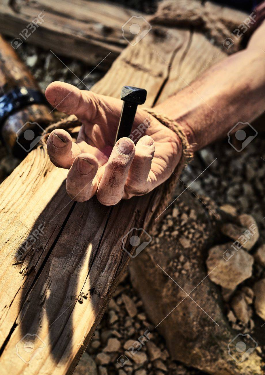 Reenactment of Jesus Christ crucifixion with human hand nailed to wooden cross in close up - 86801327
