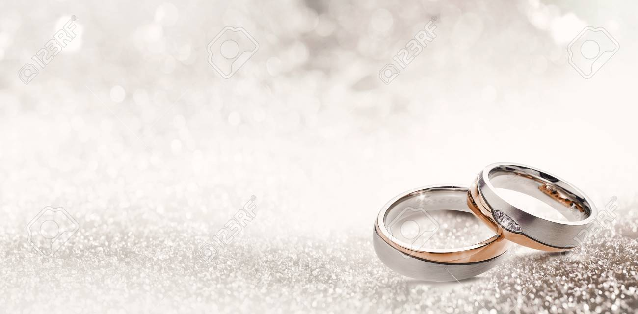 Designer wedding rings in the corner on a sparkling glitter background in panoramic banner format with copy space and selective focus - 88449792