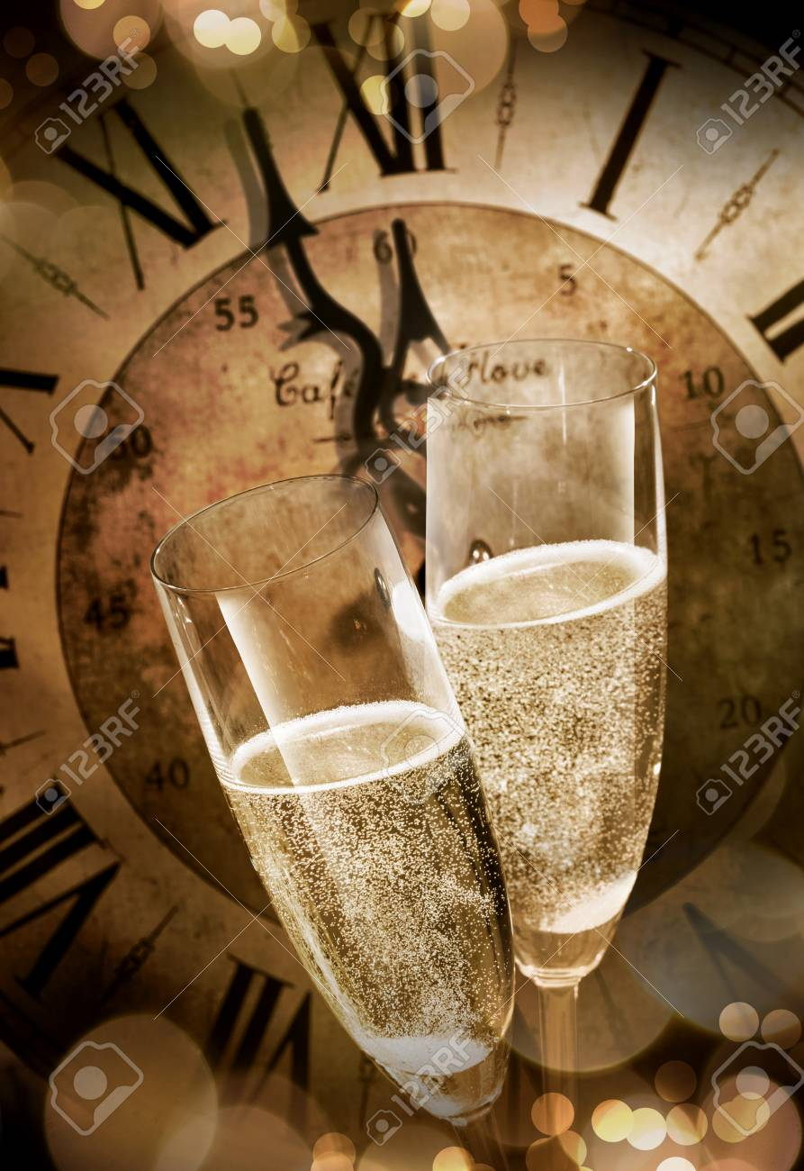 Close-up of two champagne flutes toasting before midnight against a vintage clock during romantic celebration at New Years Eve - 89756894