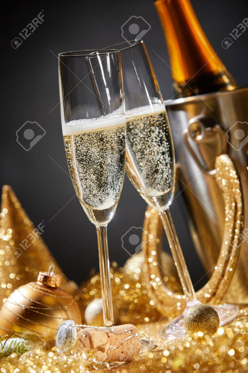 new year card with two champagne flutes surrounded by golden christmas ornaments during romantic party or