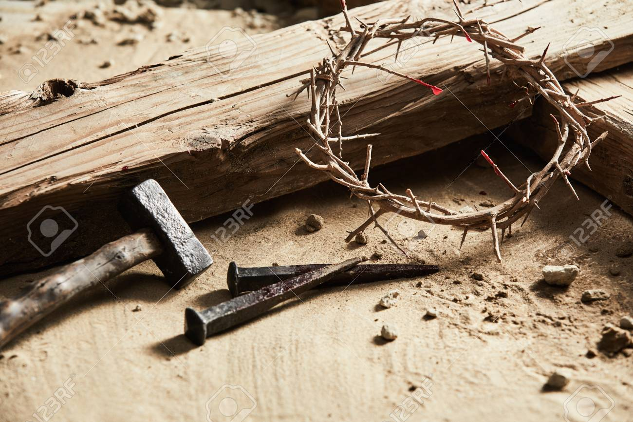 Easter background depicting the crucifixion with a rustic wooden cross, hammer, nails and crown of thorns in a close up cropped view on sand - 96322722