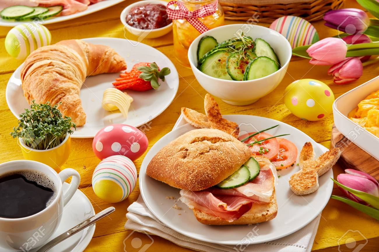 Tasty Easter brunch or spring breakfast with a fresh croissant, ham or bacon roll and coffee on a table decorated with colorful Easter eggs and tulips - 96339386