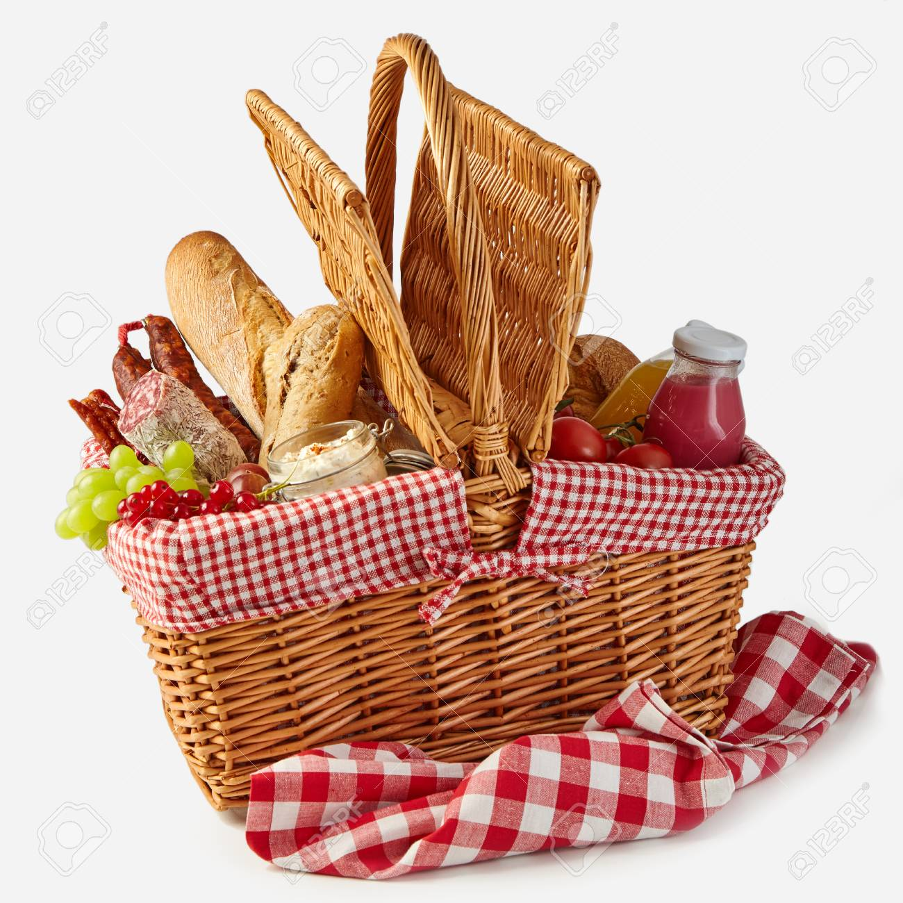 Summer picnic basket filled with food with fresh fruit and juice, spicy salami, baguettes, tomatoes and herb spread isolated on white on a rustic checked tablecloth - 104039865