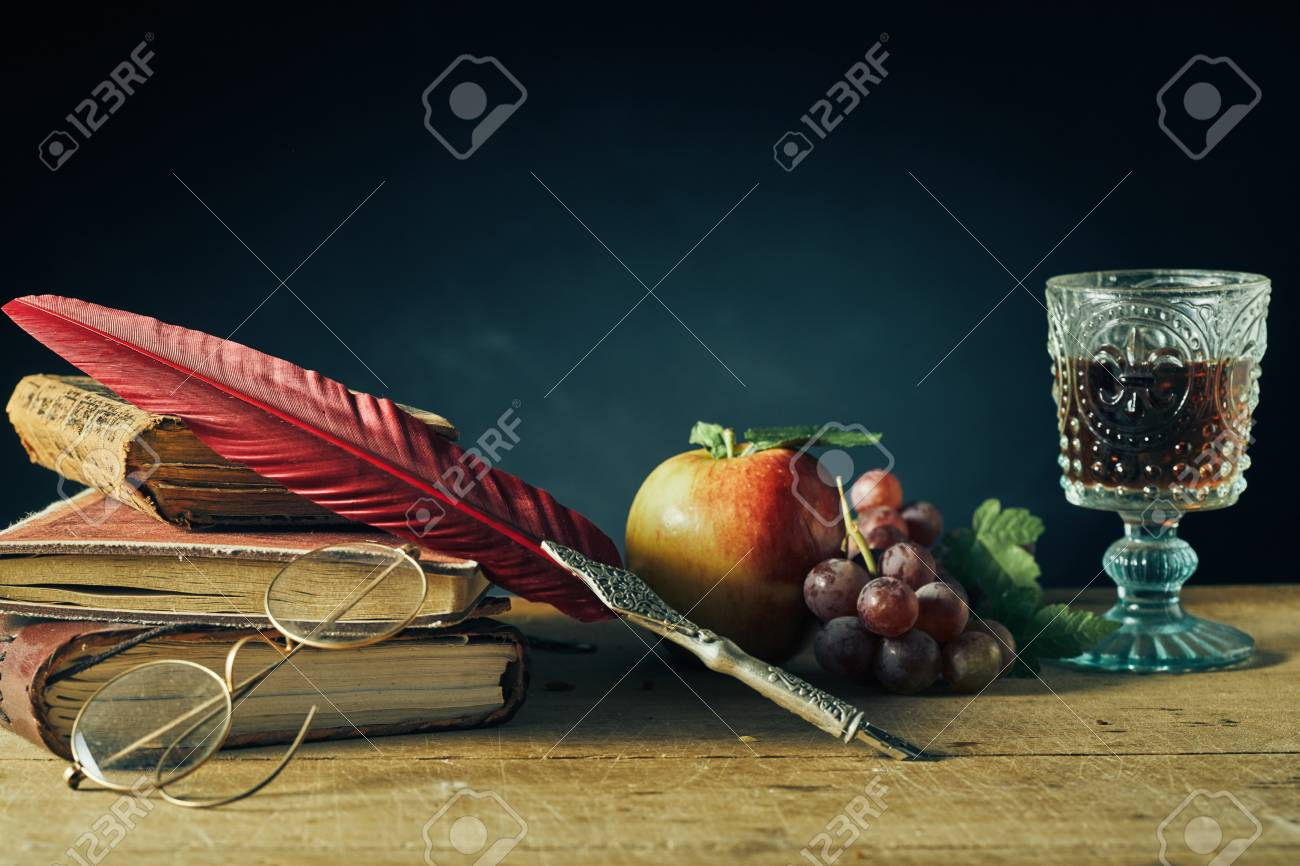 Vintage still life for college or a writer with a feather quill pen and reading glasses resting on old books alongside fresh grapes, an apple and goblet of wine on an old wooden table with copy space - 104943512