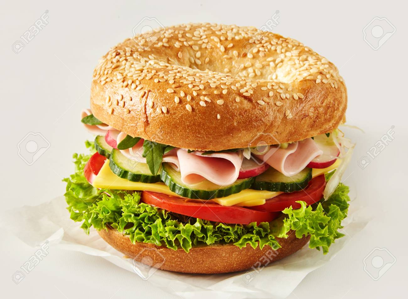 Crusty sesame bun or bagel with ham, cheese and salad filling on paper over white for advertising or a menu - 106485564