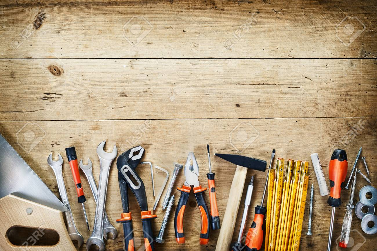 Bottom border of assorted hand tools arranged in a neat row conceptual of DIY, renovations, repair, building and woodworking over wood with copy space and vignette - 107768409