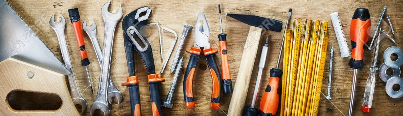 Panorama banner of assorted hand tools on wood for renovations, DIY, building and construction or woodworking - 110596902
