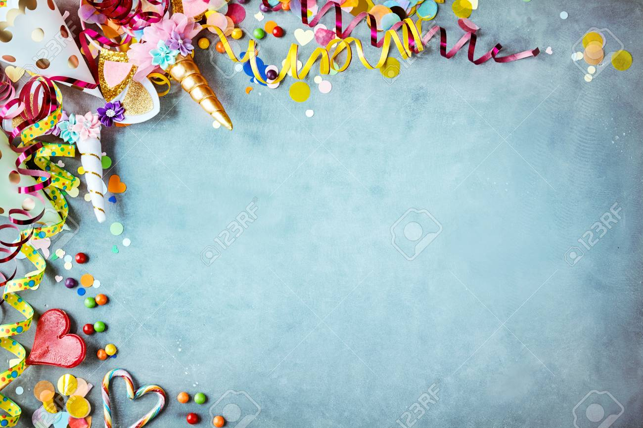 Colorful unicorn carnival border over a cool blue textured background with copy space with party hats, candy, streamers and hearts - 108238231