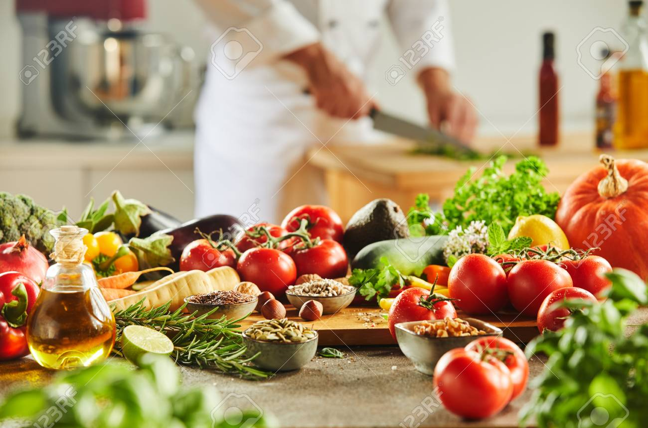 Cutting board completely covered with assorted food and man in chef outfit chopping herbs in background - 109220203