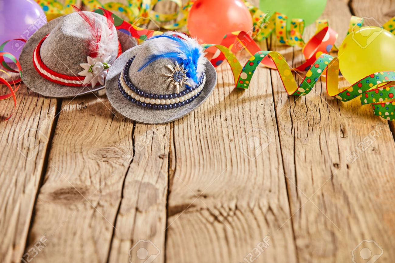 Small hats with feathers stuck in them and round multicolored balloons sitting on rustic wooden table - 110080823