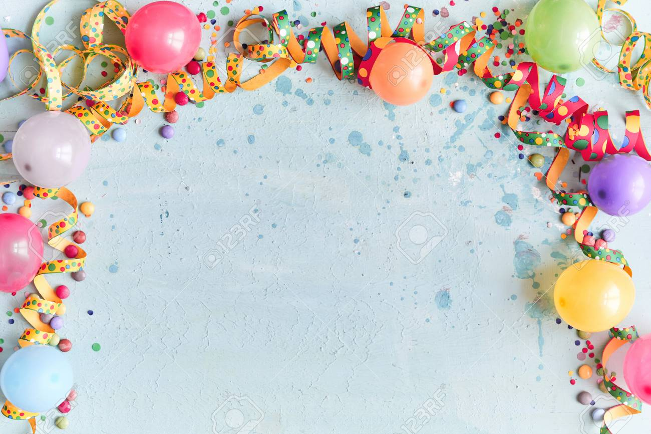 Carnival, festival or birthday balloon background with colorful party streamers, candy and confetti making a border on a blue background with copy space - 110130273