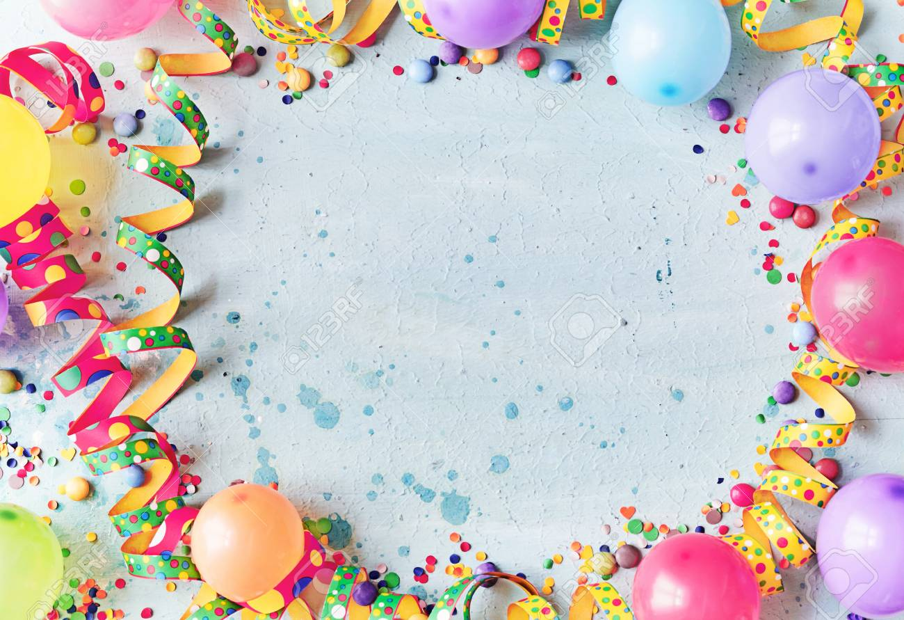 Multicolored carnival or birthday background on blue with a frame of colorful party balloons, streamers, confetti and candy around central copy space - 110130431