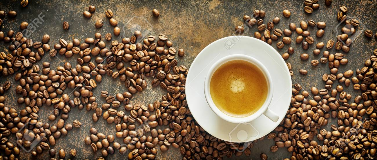 Panorama banner with roasted coffee beans and a generic white cup and saucer of milky latte coffee on a textured slate background viewed from above - 110778282