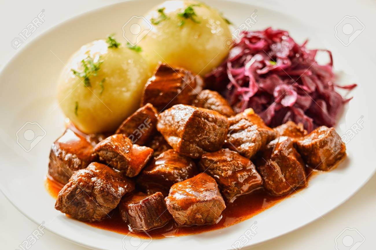 Wild venison goulash or hot pot served with dumplings and red cabbage in a close up side view for advertising - 115257642