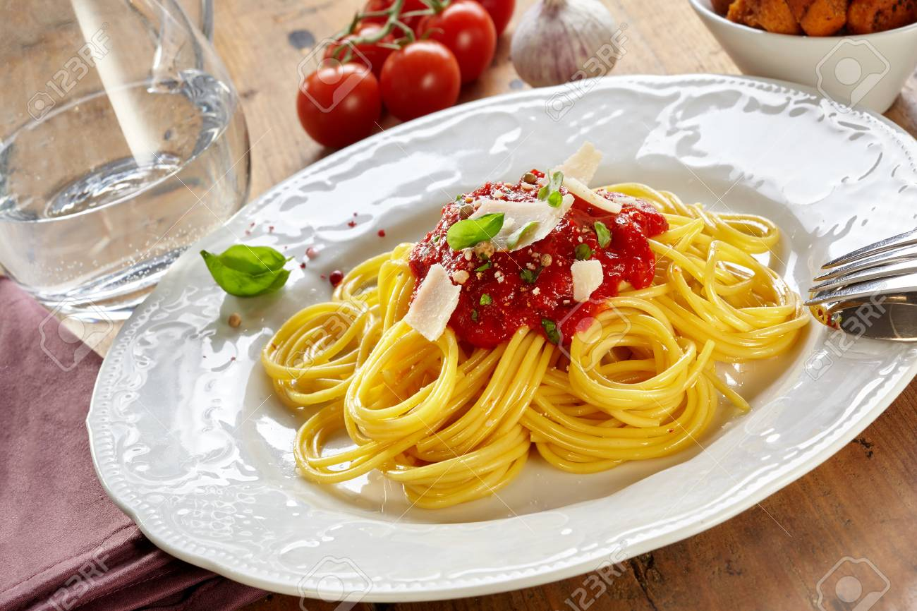 Plate of spaghetti Bolognaise or Bolognese with a tomato and herb topping sprinkled wth parmesan cheese in a tilted view on a wooden table - 115257795