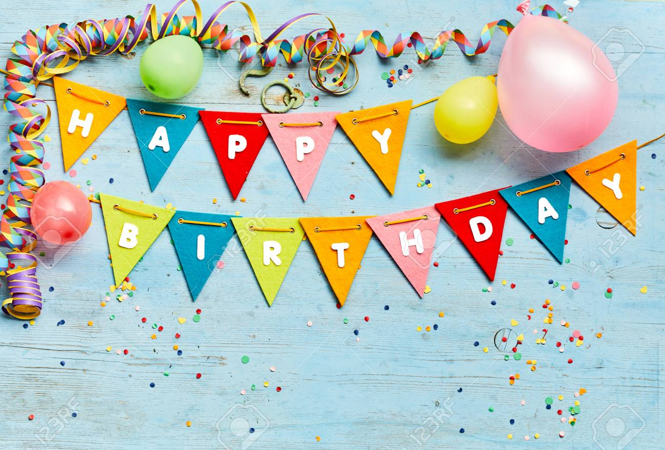 Happy Birthday bunting background with colorful triangular flags, party balloons, streamers and confetti on a blue wood background with copy space - 115257925